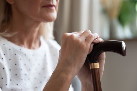 50s woman holding walking stick close up arms and wooden cane, difficult to move without support, help during rehabilitation, physical impairment, senile disease, chronic movement disorder concept