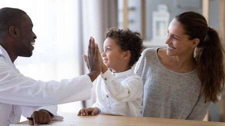 Happy african american young male doctor giving high five to smiling mixed race little kid boy, celebrating good result of prescribed medical treatment or welcoming new patient with mum at clinic.