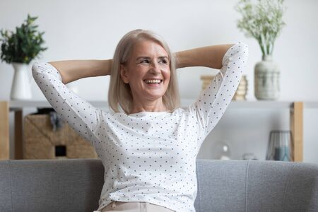 Satisfied middle-aged 60s woman sitting on couch put hands behind head smiling enjoy carefree time at home, no stress and anxiety, reducing fatigue and tiredness, relish of retired calm life concept