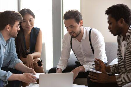 El equipo calificado de jóvenes profesionales, el personal de la empresa multiétnica que trabaja en un proyecto rentable juntos, sentados en el sofá de la oficina moderna, participa en la consideración de los problemas actuales comunes para resolver el concepto