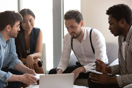 Skilled team of young professionals multiethnic company staff working on profitable project together seated on couch in modern office take part in consideration common current issues solving concept