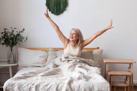 Erfrischte ältere 50er-Jahre-Frauen wachen morgens auf, sitzend im Bett im hellen Schlafzimmer zu Hause, Frau mittleren Alters fühlt sich nach genügend Schlaf glücklich und schwungvoll, begrüßt den neuen Tag, guten Morgen-Konzept