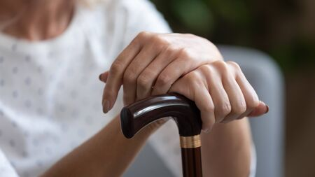 Close up horizontal image elderly woman holds wooden cane sitting at home or nursing house, concept of senile illness, physical damage, chronic progressive movement disorder Parkinson disease concept