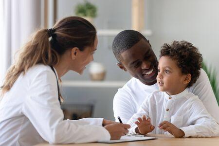 Pediatra joven alegre y padre sonriente afroamericano escuchando al pequeño paciente de raza mixta, diciéndole al médico sobre el bienestar. Feliz familia multirracial visitando la clínica para chequeo. Foto de archivo