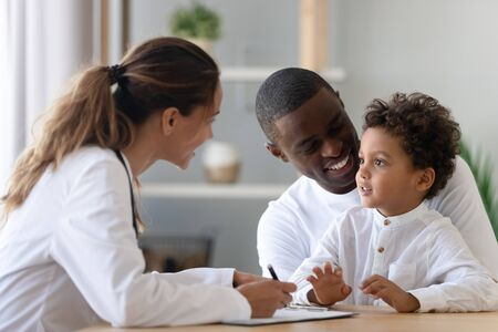 Vrolijke jonge vrouwelijke kinderarts en Afro-Amerikaanse glimlachende vader die luistert naar een kleine patiënt van gemengd ras, die de dokter vertelt over welzijn. Gelukkige multiraciale familie die kliniek bezoekt voor controle. Stockfoto