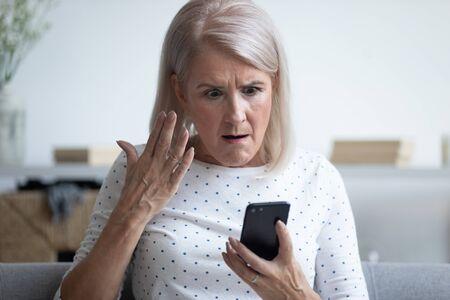 Oudere 50-er jaren vrouw zittend op de bank in de woonkamer met een smartphone gebarend kijkend geïrriteerd voelt zich boos als ze een probleem heeft met gadget, traag internet, verbinding verbroken, ontladen gebroken apparaatconcept