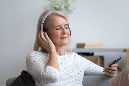 Close up of elderly 50s woman resting on couch in living room wearing wireless headphones holds smart phone listens favorite music using online application in internet, pastime at retired life concept