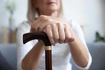 Close up focus on female hands holding wooden walking stick cane as symbol of physical chronic disability, handicapped person, movement disorder, Parkinson disease, need caretaker social issue concept