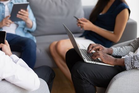 Businesspeople seated on couch using laptop, smartphone, tablet do work online, gadget era people use their devices to grab information, interact all time distantly, active uses of cyberspace concept Banco de Imagens