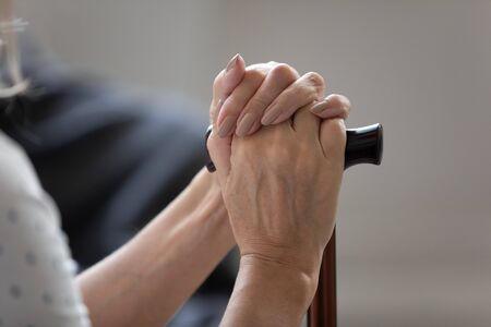 Close up image senior female hands holding walking stick sitting indoors, concept of disabled retired woman having health problems walking disorder, abandoned unhappy unhealthy human at nursing home