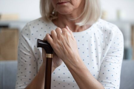Close up focus on cane and arms of depressed disabled retired woman hold walking stick, female goes through rehabilitation, suffers from chronic progressive Parkinson disease movement disorder concept