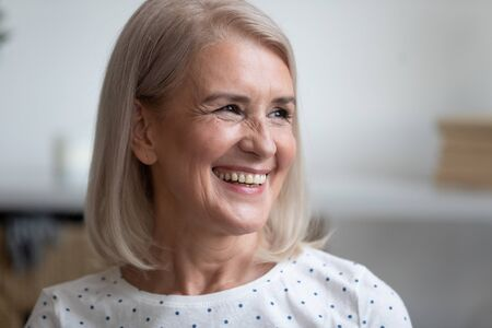 Close up portrait happy aged woman with candid wide white smile looks away, pretty middle-aged female posing indoors feels satisfied spend time at home, natural looking beauty, healthy retiree concept Stock fotó