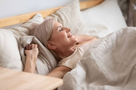 Middle-aged attractive woman lying in bed on comfortable memory foam pillow fresh beige color bed clothes enjoying early morning awakened at home closed eyes dreaming visualizing perfect day concept