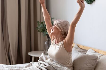 Happy rested awakened woman stretching raised her hands after waking up sitting in bed at home. Concept of refreshed renewed strength and energy, enough night sleep, start new day good morning concept