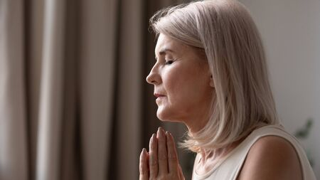 Close up horizontal image side view face of middle-aged woman folded hands together in prayer mentally speaking asking God for help. Religious sincere person, make frank strong wish, worship concept 版權商用圖片