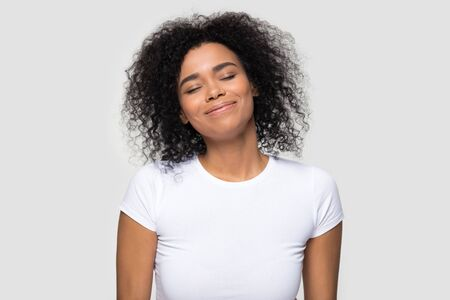 Satisfied calm African American woman enjoying fresh air, good smell, dreaming about future with closed eyes, smiling pleased peaceful young female with curly hair isolated on studio background