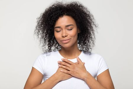 Grateful hopeful African American woman holding hands on chest, pleased young female with closed eyes feeling love, gratitude, appreciation, thanking fate, isolated on studio background