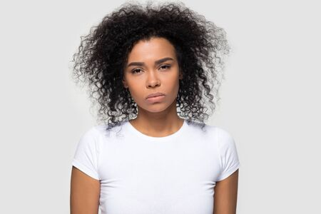 Dissatisfied millennial African American woman looking at camera, showing negative attitude, headshot portrait irritated young female wearing white t-shirt, isolated on studio background