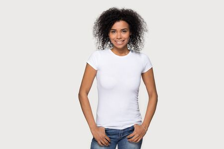 Smiling African American woman in jeans and blank white t-shirt front mock up, attractive young female demonstrate clothes design template copy space for print, isolated on studio background