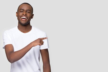 Happy African American man with healthy white smile pointing finger at copy space, looking at camera, satisfied client customer showing great shopping offer, sale isolated on studio background Foto de archivo
