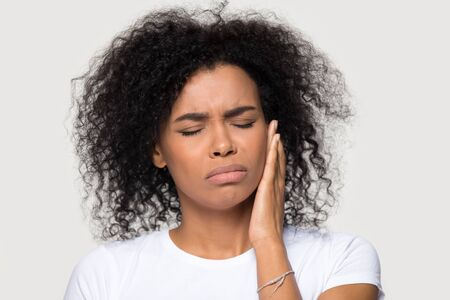 Unhappy upset African American woman suffering from tooth pain close up, teeth problem, frustrated sad young female feeling painful toothache, touching cheek, isolated on studio background Banque d'images