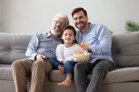 Cheerful caucasian 60s grandfather grown up son and little grandchild sitting on couch use remote control watching movie eating pop corn Stockfoto