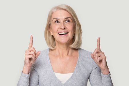 Happy mature woman look up showing up with fingers portrait. Stock Photo