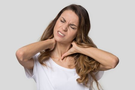 Tired unhappy young woman massaging tensed neck muscles