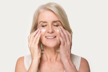 Smiling mature woman applying rejuvenating cream on her face skin.