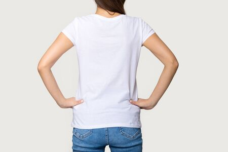 Millennial female wearing mock up t-shirt standing turning back to camera.