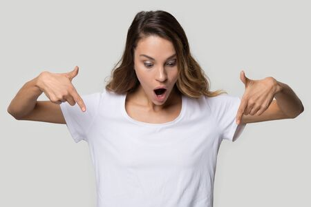 Excited young woman with open mouth pointing finger down