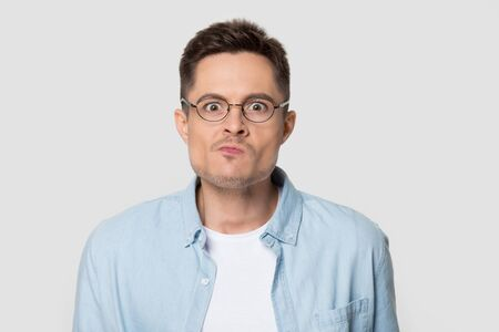 Headshot of confused angry man in eyeglasses looking at camera. Portrait of frustrated stylish male emotionally pressing his lips with furious look wearing glasses. Model posing for studio photoshoot