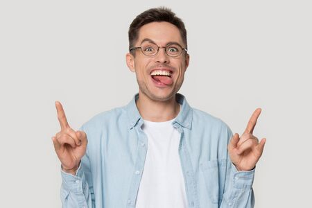 Portrait of funny crazy happy handsome millennial man in eyeglasses showing rock-n-roll gesture with stuck out tongue, pretending to be rock star, having fun, isolated on grey studio background.