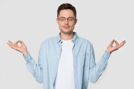Relaxed millennial man standing meditating at studio with eyes closed. Male model posing for photoshoot wearing glasses isolated. Emotion control, yoga, calmness, rest, relaxation, meditation concept