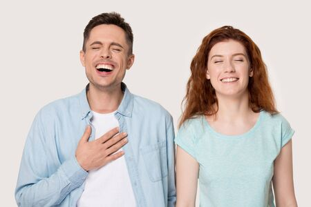 Sincere young family couple laughing portrait, handsome man and attractive woman laughing at joke, having fun together, happy to hear perfect news, isolated on grey white studio background.