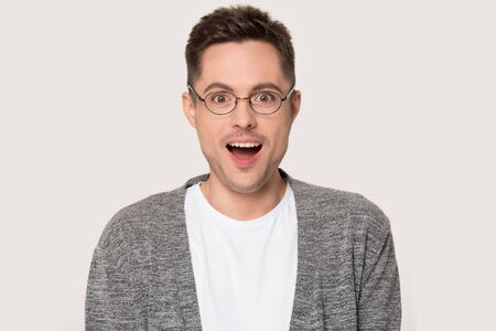 Headshot of surprised millennial man with opened mouth from wonder. Astonished, amazed male wearing eyeglasses looking at camera isolated on grey background in studio. Wonderment, astonishment concept