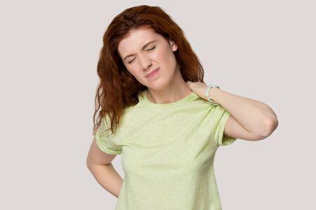 Portrait en studio d'une jeune femme rousse souffrant de fortes douleurs au dos, de terribles douleurs au cou, une fille millénaire fatiguée a des tensions ou des spasmes corporels, des problèmes de santé, une mauvaise posture, isolée sur fond.