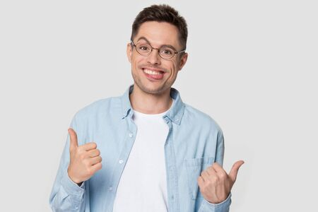 Young man with funny nerd jerk face showing thumb up. Smiling male model posing to camera with tongue out wearing glasses. Person portrait in photo studio during photoshoot isolated on gray background