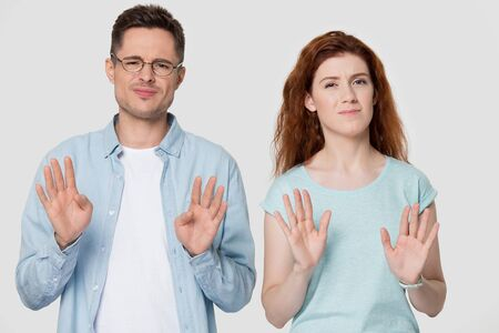 Handsome young man in eyeglasses and millennial red hair woman family couple refusing bad deal offer, rejecting sale proposition, gesturing no, isolated on grey white studio background.