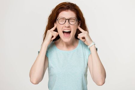 Annoyed stressed angry woman sticking plug fingers in ears, crazy red-haired woman screaming in tantrum, suffering from loud sounds or noisy neighbors, isolated on grey white studio background.