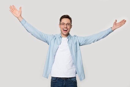 Overjoyed happy man standing with his hands wide open. Laughing male model posing at studio photoshoot want to hug person. Image of kind cheerful guy isolated on grey background. Invitation concept Banco de Imagens