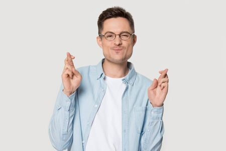 Confident handsome man in shirt cross fingers praying for luck. Portrait of funny male model wearing glasses standing against gray background isolated begging for good, holding eyebrow up, press lips