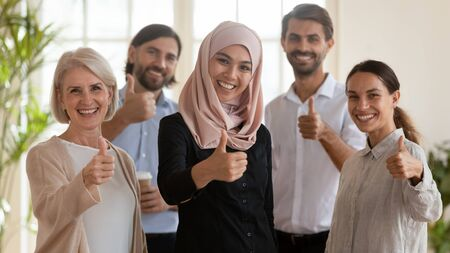Head shot portrait of smiling successful multiracial group of younger and older business people with arabic female team leader in hijab showing thumbs up gesture, looking at camera, feeling happy.