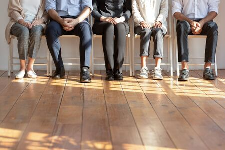Close up cropped image of diverse people sitting on chairs in row. Five diverse female and male candidates waiting patiently for dream job interview in queue, human resources, recruit process concept.