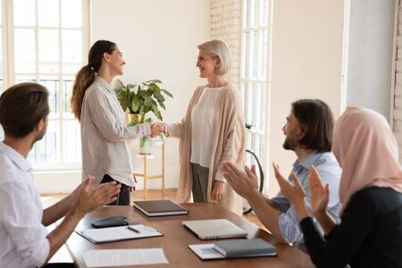 Satisfied with good job results smiling older team leader shaking hands with happy female colleague while diverse teammates clapping hands. Smiling boss praising coworker at business meeting.