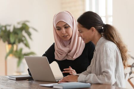 Concentrated young arabian woman in hijab sitting with smiling colleague at table, looking at computer screen, explaining new company software. Focused team leader training millennial female intern. Stockfoto