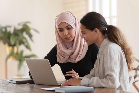 Geconcentreerde jonge arabische vrouw in hijab zittend met lachende collega aan tafel, kijkend naar computerscherm, nieuwe bedrijfssoftware uitleggend. Gerichte teamleider die millennial vrouwelijke stagiaire opleidt.