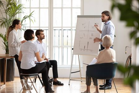Full length serious young male professional standing near flipchart, explaining drawn graphs to focused mixed race coworkers. Speaker holding educational seminar or workshop for business people.