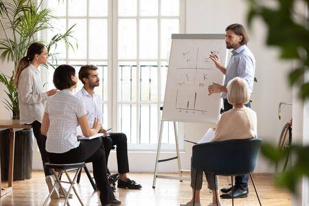 Profesional masculino joven serio de longitud completa de pie cerca del rotafolio, explicando gráficos dibujados a compañeros de trabajo de raza mixta enfocados. Ponente con seminario educativo o taller para empresarios.