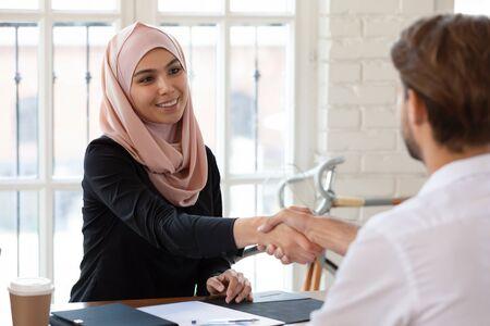Aangename lachende arabische vrouwelijke hr-manager in hijab handen schudden met mannelijke sollicitant. Jonge gelukkige arabische zakenvrouw verwelkomende partner of maken een overeenkomst met de klant tijdens een bijeenkomst op kantoor. Stockfoto